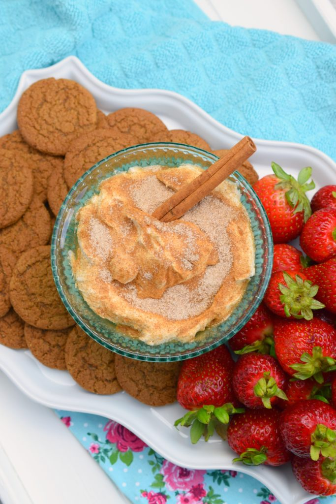 floral and blue fabric under white dish holding bowl of creamy churro dip along with cookies and strawberries
