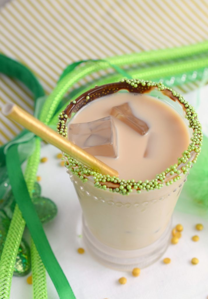 overhead shot of cocktail with gold straw and assorted green St. Patrick's Day decor